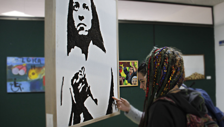 Hall de exposiciones, dos estudiantes observando un cuadro expuesto.